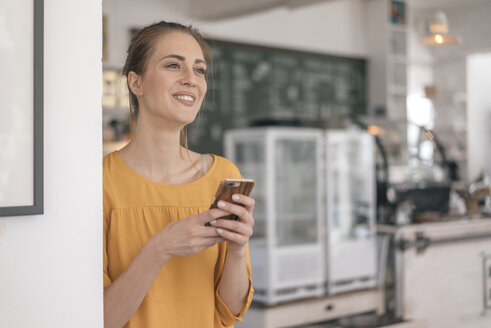 Young business owner standing in her coffee shop, using smartphone - JOSF02327