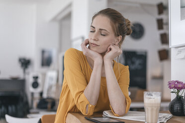 Young woman working in coworking space, closing eyes - JOSF02330