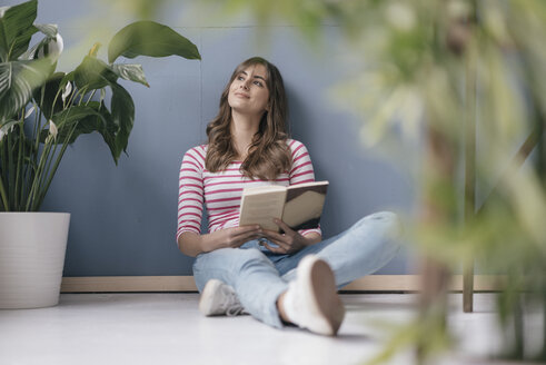 Woman sitting on ground in her new home, reading a book, surrounded by plants - JOSF02366