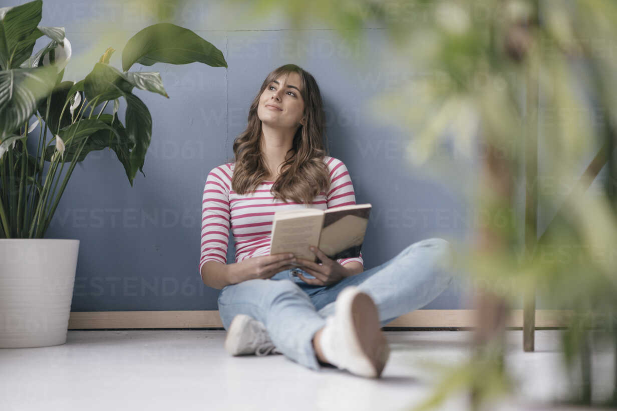 Woman sitting on ground in her new home, reading a book, surrounded by plants - JOSF02366 - Joseffson/Westend61