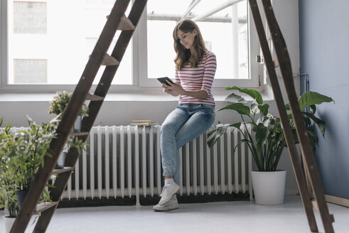 Woman sitting on radiator in her new home, reading e-book, surrounded by plants - JOSF02369