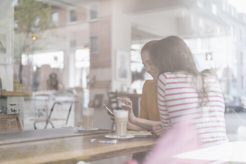 Two girlfriends meeting in a coffee shop, using smartphone - JOSF02381