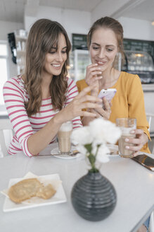 Two girlfriends meeting in a coffee shop, using smartphone - JOSF02390