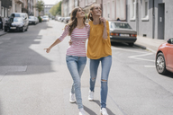 Two girlfriends having fun in the city, walking arm in arm - JOSF02396