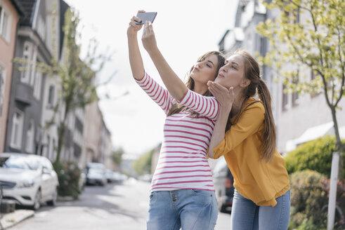 Girlfriends taking selfie in the city - JOSF02405