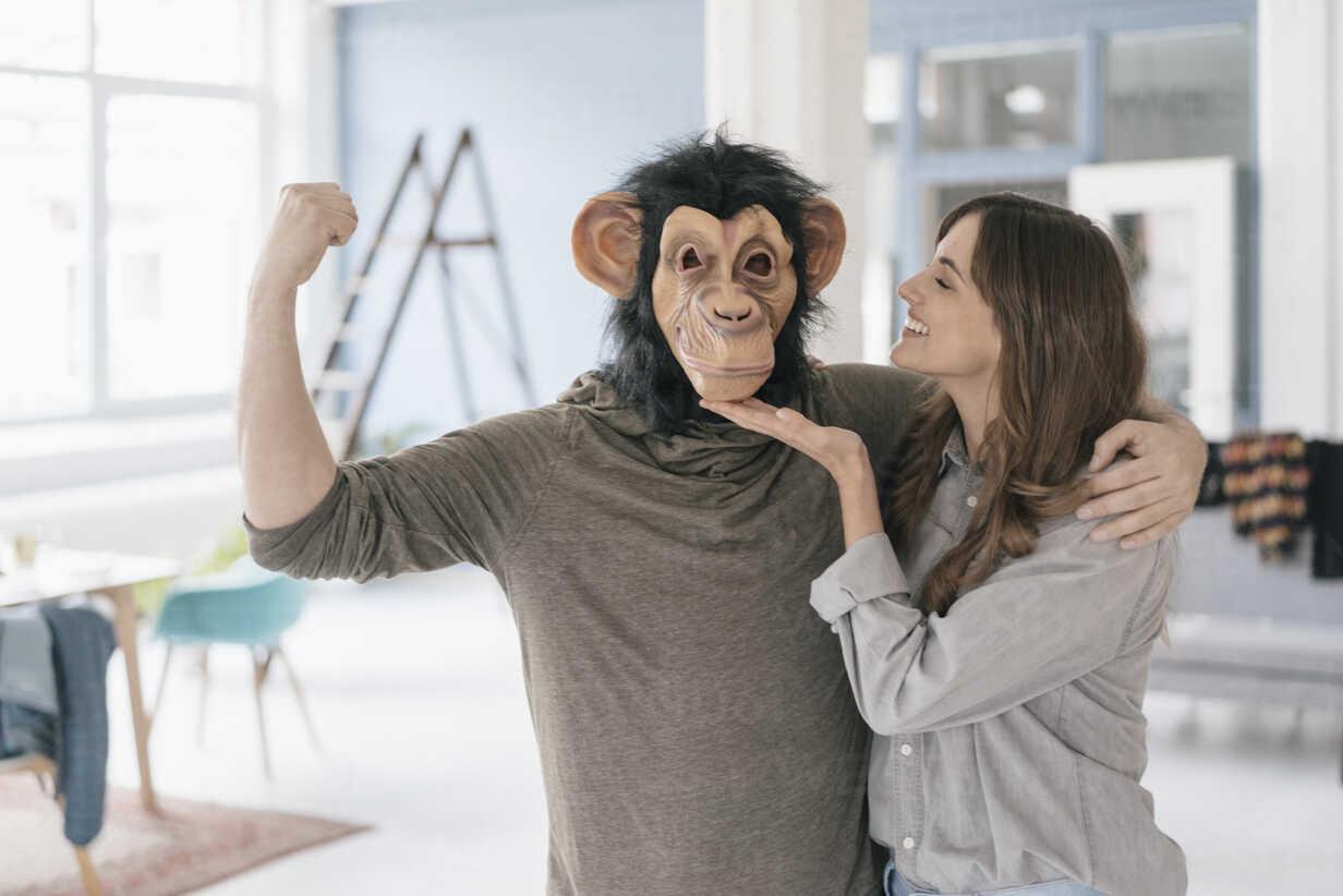 Man wearing chimpanzee mask, flexing muscles, woman petting him - JOSF02408 - Joseffson/Westend61