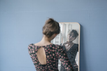Young woman in vintage dress looking into mirror - JOSF02420