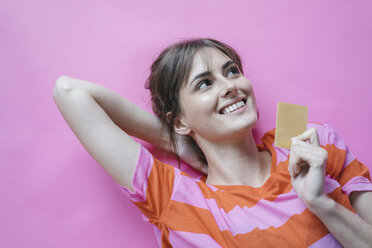 Woman lying on pink background with hands behind head, holding credit card - JOSF02423