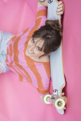 Woman holding skateboard, looking up - JOSF02426