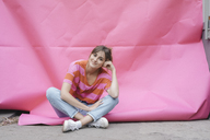 Confident young woman sitting on pink background - JOSF02429