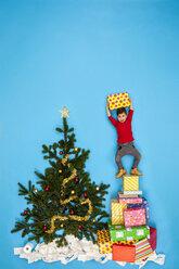 Boy standing on pile of Christmas presents next to Christmas tree - BAEF01634