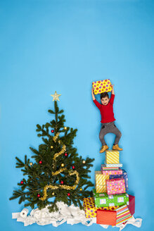 Boy standing on pile of Christmas presents next to Christmas tree - BAEF01634