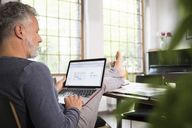 Mature man working from his home office with feet up, using laptop - FKF03041