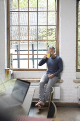 Mture man taking a break, drinking coffee at the window of his loft apartment - FKF03047
