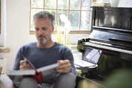 Laptop on stool in front of piano, man reading in book - FKF03050