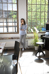 Woman standing at window of her loft apartment, drinking coffee - FKF03053
