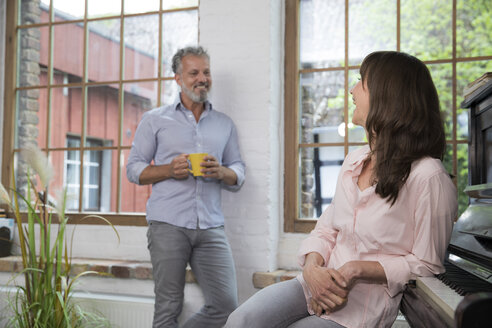 Mature couple at home taking a break, talking and drinking coffee - FKF03062