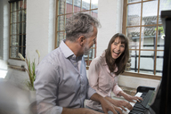 Mature couple having fun at home, playing the piano - FKF03068