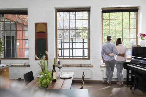 Mature couple standing in their comfortable loft, looking out of window, rear view - FKF03077
