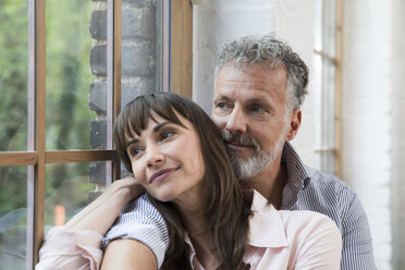 Mature couple sitting on window sill, looking out of window - FKF03080