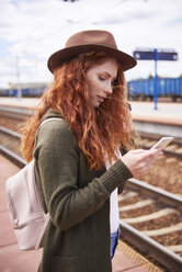 Redheaded woman wearing hat standing at platform looking at cell phone - ABIF00760