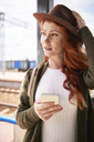 Portrait of redheaded woman with hat and smartphone at platform - ABIF00763