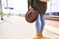Woman with brown hat waiting at platform, partial view - ABIF00766