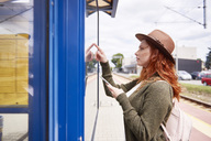 Redheaded young woman looking at timetable on platform - ABIF00769