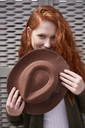 Portrait of smiling redheaded woman with brown hat - ABIF00772