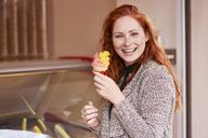 Portrait of happy redheaded woman with ice cream cone - ABIF00775