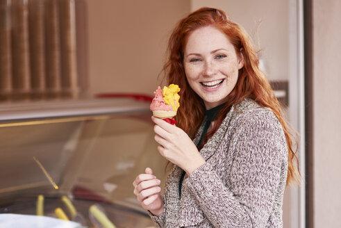 Portrait of happy redheaded woman with ice cream cone - ABIF00775