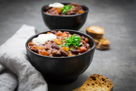 Bowl of Chili con Carne with fresh coriander and sour cream - LVF07343