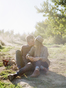 Apple orchard. A couple sitting on a sunlit path. - MINF02275