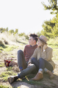 Apple orchard. Couple sitting on the ground, a basket of apples. - MINF02293