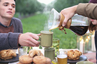 Apple orchard. Group of people sitting round a table with food and drink, pouring coffee. - MINF02299