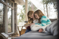 Two girls sitting on a sofa, reading a book. - MINF02302