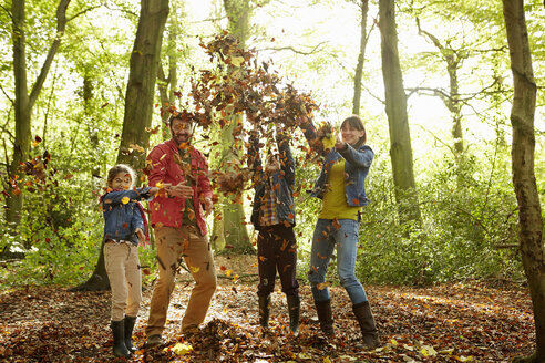 A family throwing dried leaves into the air in the woods in autumn. - MINF02467