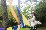 A woman in a Kyoto park holding up a colourful row of flags. - MINF02527