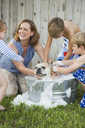 A family in their garden, washing a dog in a tub. - MINF02638
