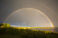 A double rainbow in the sky arching over the land. - MINF02656