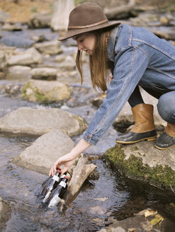 Young blond woman wearing a hat, putting drink bottles in a river. - MINF02699