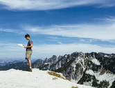 A hiker on the mountain summit, looking at a map. Surprise Mountain, Alpine Lakes Wilderness, in Mount Baker-Snoqualmie National Forest, - MINF02723