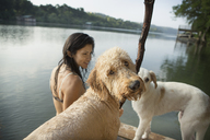 A woman swimming with her two dogs in a lake. - MINF02735