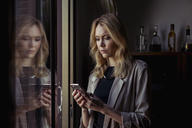 Portrait of blond young woman looking at cell phone - MAUF01518