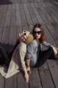 Portrait of two fashionable young women sitting on wooden floor wearing sunglasses - MAUF01530