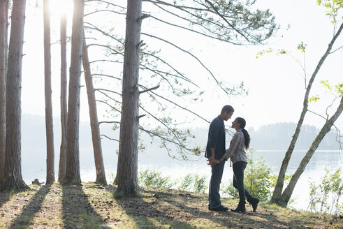 Lakeside.  A couple walking in the shade of pine trees in summer. - MINF02851