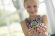 A young girl holding out a small globe in the palms of her cupped hands. - MINF02863
