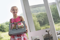 A young girl in a kitchen wearing a pink dress.  Carrying a terrarium containing small plants. - MINF02866