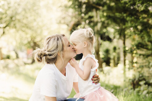 Happy mother kissing her little daughter outdoors - NMSF00217