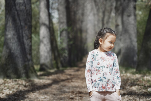 Littele girl standing in park, with hands in pockets - AZF00012